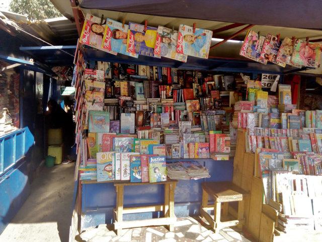 Un stand de livres d'occasion situé en premier plan à Ambohijatovo