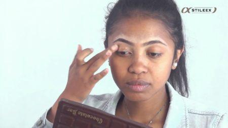 La première étape du maquillage gold and brown implique l'application de la base pour paupières