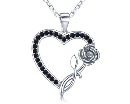 Un pendentif cœur en argent avec sa chaîne, et terminé par une rose. Notez la présence de cristaux noirs qui donnent un ton soutenu à l'ensemble.